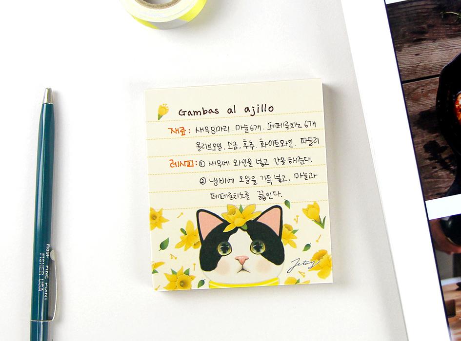 頭に黄色のお花を乗っけた<br>とてもキュートな<br>ハチワレ猫が魅力的な<br>【白黒イエローフラワー】のメモパッド♪